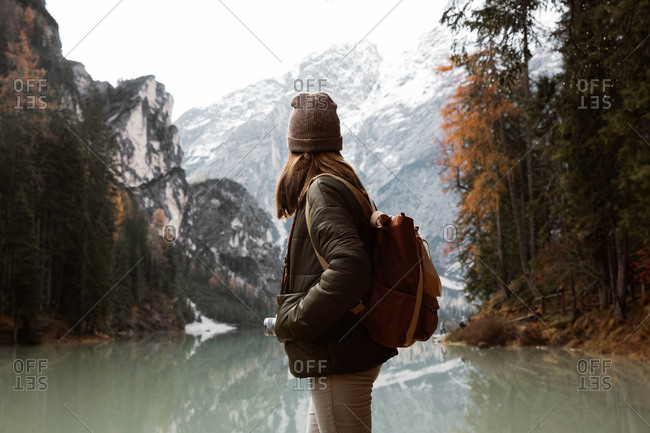 Back view of anonymous woman traveler in casual wear with backpack standing and delighting in view of turquoise lake with foggy Dolomites mountains on background at Italy