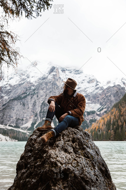 Hipster man traveler in casual wear sitting in a rock delighting in view of turquoise lake with foggy Dolomites mountains on background at Italy