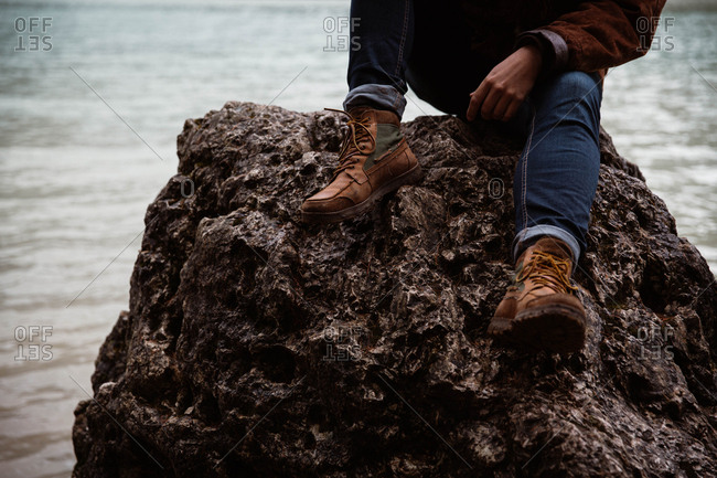 Anonymous cropped man traveler in casual wear sitting in a rock delighting in view of turquoise lake with foggy Dolomites mountains on background at Italy