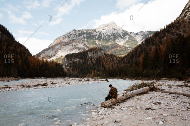 Back view of anonymous man traveler in casual wear sitting in a fallen tree trunk delighting in view of turquoise lake with foggy Dolomites mountains on background at Italy