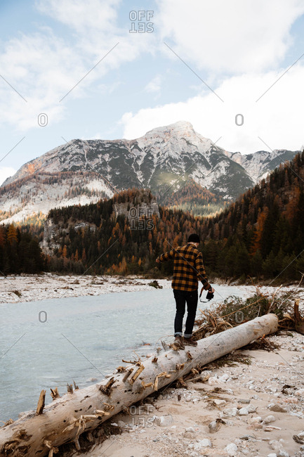 Back view of man traveler in casual wear with a professional camera walking in a fallen tree trunk delighting in view of turquoise lake with foggy Dolomites mountains on background at Italy