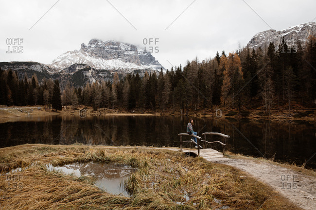 Woman traveler in casual wear sitting in a wooden bridge handrail and delighting in view of lake with Dolomites mountains on background at Italy