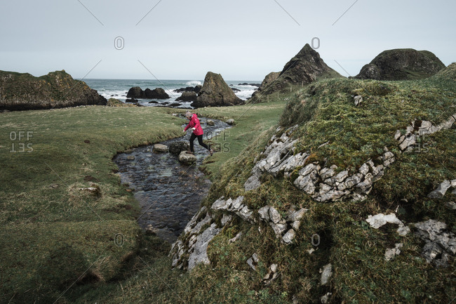 From above anonymous woman enjoying amazing scenic landscape of Northern Ireland during travel while walking near fast shallow river flowing to waters of rocky shore