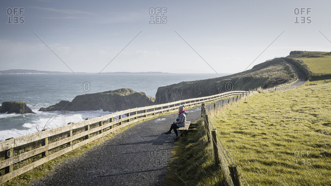 Woman sitting resting during a walk on narrow rural road along green field on sunny spring day at coastline in Northern Ireland