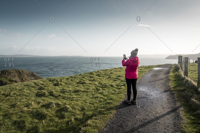 Back view of female traveler in warm activewear standing on rural road running along shore with green grass and taking photo of ocean with calm water in sunny spring day in Northern Ireland