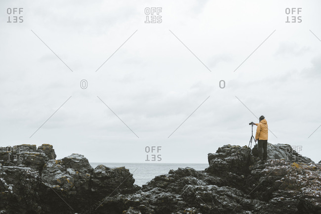 Back view of male traveler standing on rock with camera on tripod and taking picture of seascape on cloudy gloomy day on Northern Ireland coastline