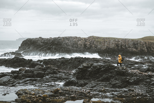 Male traveler standing on rock with camera on tripod and taking picture of seascape on cloudy gloomy day on Northern Ireland coastline