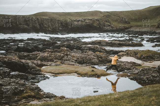 Side view of tourist jumping over puddles left with sea water on rocky shore while walking at Northern Ireland coastline on cloudy spring day