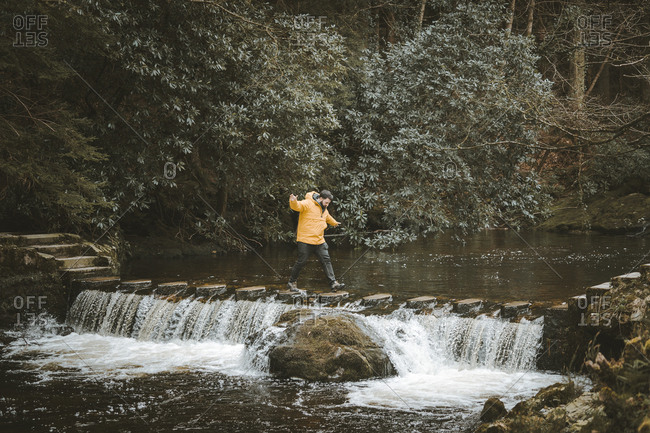 Side view of male tourist in bright orange jacket walking on footbridge and crossing river with water flowing through stepping stones in forest of Northern Ireland