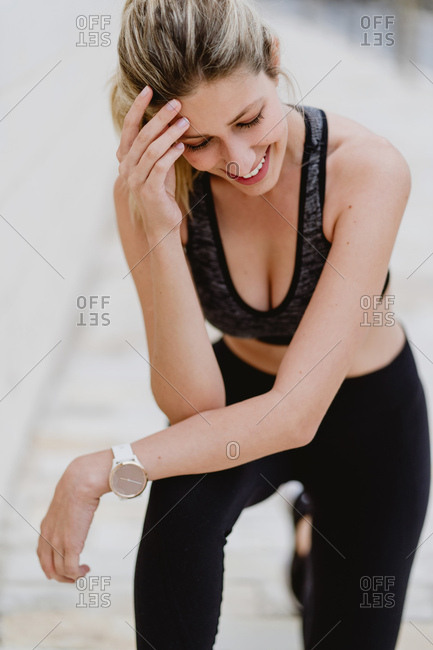Content young female athlete in stylish sports outfit with trendy watch in wrist leaning hands on knees while training
