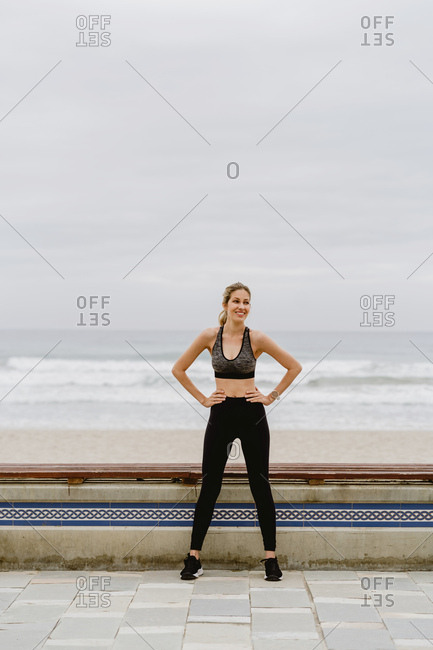 Athlete woman in active wear standing with raised hands in in lock and stretching near seashore on cloudy weather