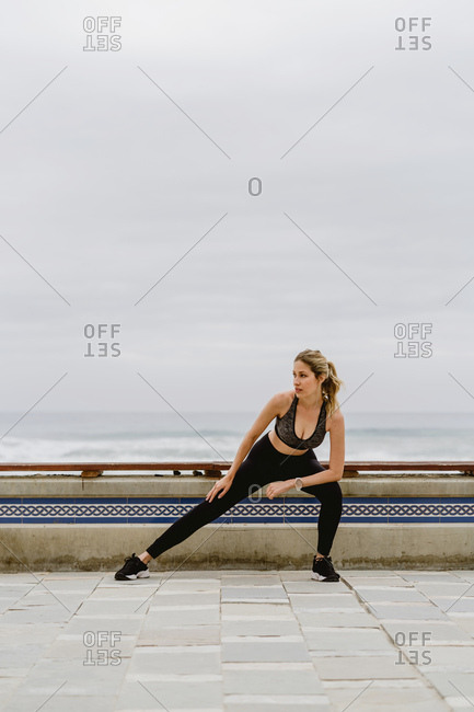 Motivated sporty woman in active wear standing stretching legs while looking away