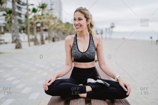 Concentrated lady athlete in trendy active wear and sneakers sitting on bench resting with legged cross looking away with seaside on blurred background