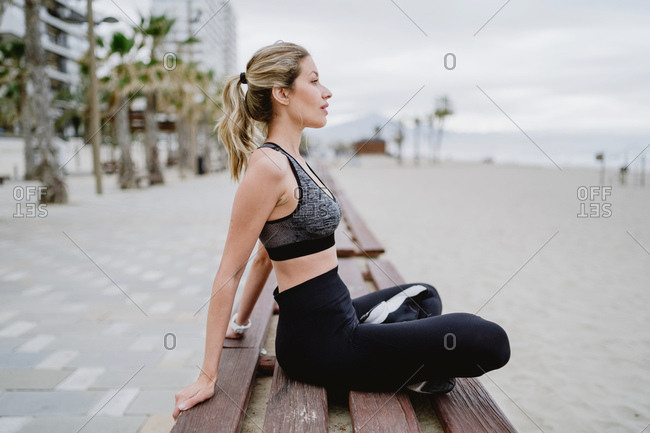 Side view of concentrated lady athlete in trendy active wear and sneakers sitting on bench resting with legged cross looking away with seaside on blurred background