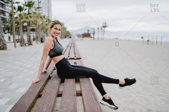 Side view of concentrated lady athlete in trendy active wear and sneakers sitting on bench resting looking at camera with seaside on blurred background