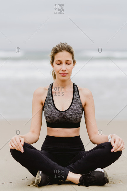Young slim female in black top and leggings sitting on lotus position at the beach with closed eyes while meditating