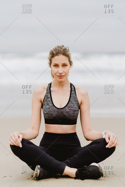 Young slim female in black top and leggings sitting on lotus position while meditating at the beach