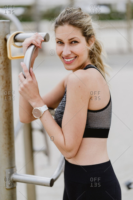 Side view of motivated sporty woman in active wear standing holding metal bar while resting at a sandy beach looking at camera
