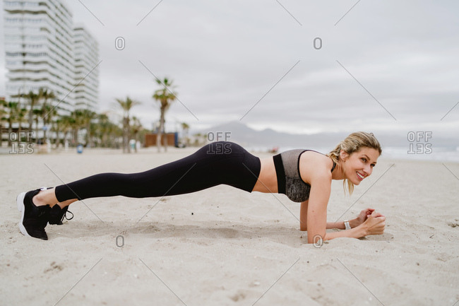 Side view of concentrated female athlete in stylish active wear and sneakers doing plank at empty sandy beach on overcast day
