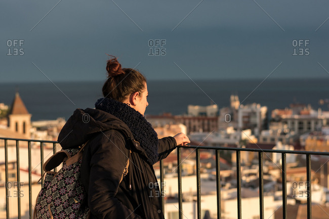 Back view of female traveler in warm clothing standing near fence and delighting in view of old city and sea in Alicante Spain