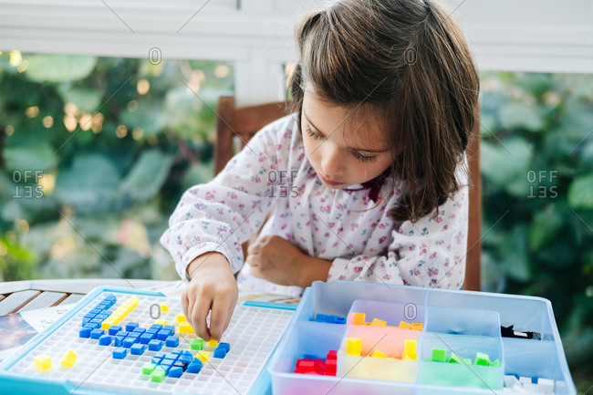 Adorable concentrated little girl putting small colorful blocks to board and creating mosaic while playing educational game