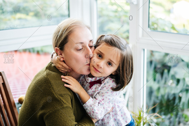 Tender loving woman sitting on chair and embracing and kissing on cheek little daughter while having happy time together on terrace