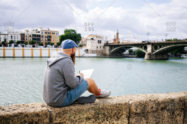Back view of bearded male art student in casual clothing sitting with crossed legs on rocked fence of quay and drawing sketches in small album with river and bridge on background