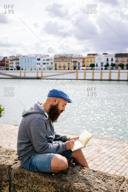 Bearded male art student in casual clothing sitting with crossed legs on rocked fence of quay and drawing sketches in small album with river and bridge on background