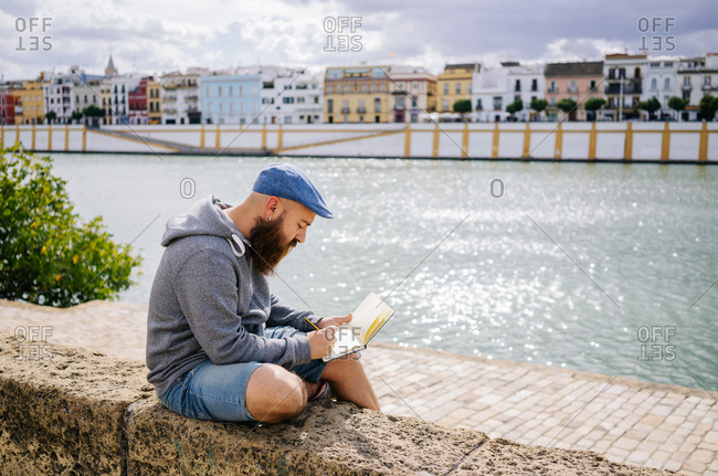 Side view of bearded male art student in casual clothing sitting with crossed legs on rocked fence of quay and drawing sketches in small album with river and bridge on background