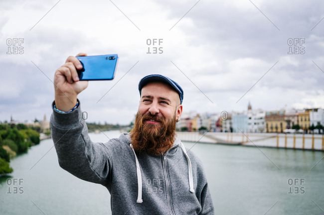 Content male traveler in casual clothing smiling and making selfie and peace sign on mobile phone while sitting on rocked fence of quay