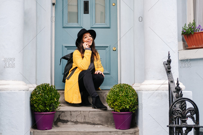 Cheerful woman in stylish yellow coat and hat smiling and looking away while sitting near potted plants and door and answering phone call on street of London, United Kingdom