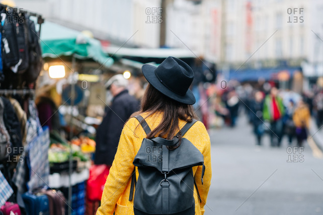 Back view of anonymous woman in yellow coat and stylish hat walking on road during carnival in London, United Kingdom