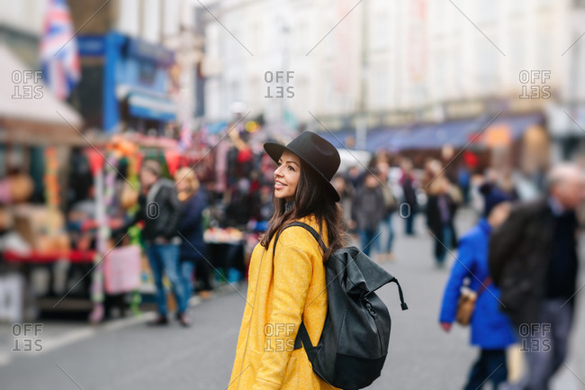 Woman in yellow coat and stylish hat walking on road during carnival in London, United Kingdom