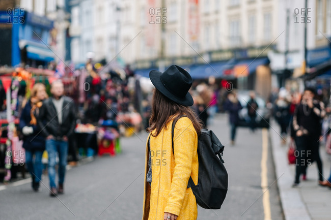 Side view of anonymous woman in yellow coat and stylish hat walking on road during carnival in London, United Kingdom