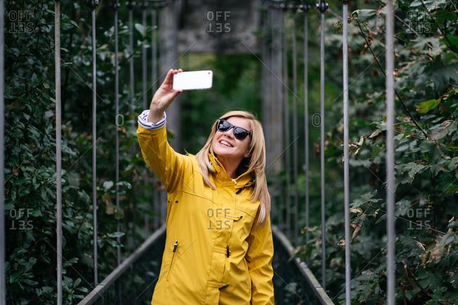 Happy female traveler taking selfie on suspension bridge in summer