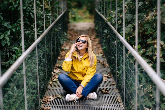 Happy female traveler talking phone on suspension bridge in summer