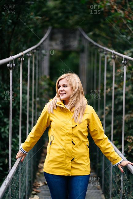 Cheerful female tourist standing on hanging bridge in summer