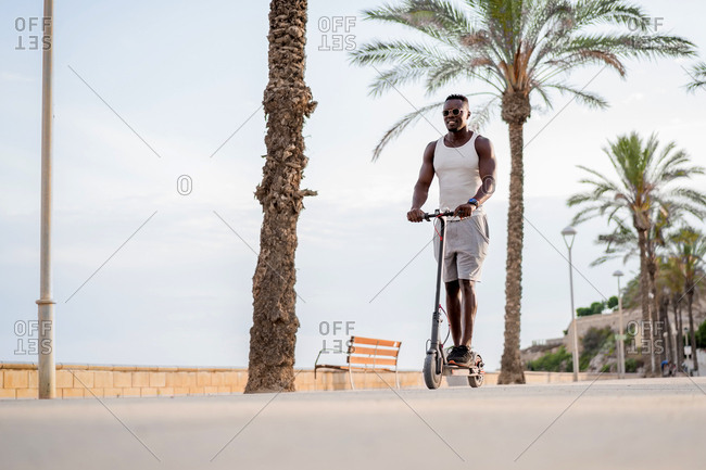 From below cheerful adult sportive African American male rider in casual clothes having fun while driving electric scooter in promenade in tropical location