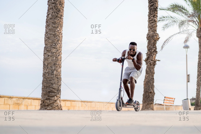 Cheerful adult sportive African American male rider in casual clothes having fun while driving electric scooter in promenade in tropical location