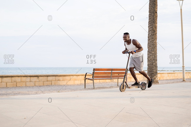 Side view of cheerful adult sportive African American male rider in casual clothes having fun while driving electric scooter in promenade in tropical location