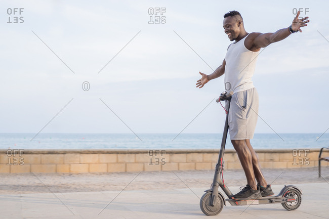 Side view of cheerful adult sportive African American male rider in casual clothes having fun while driving electric scooter in promenade in tropical location with raising hands