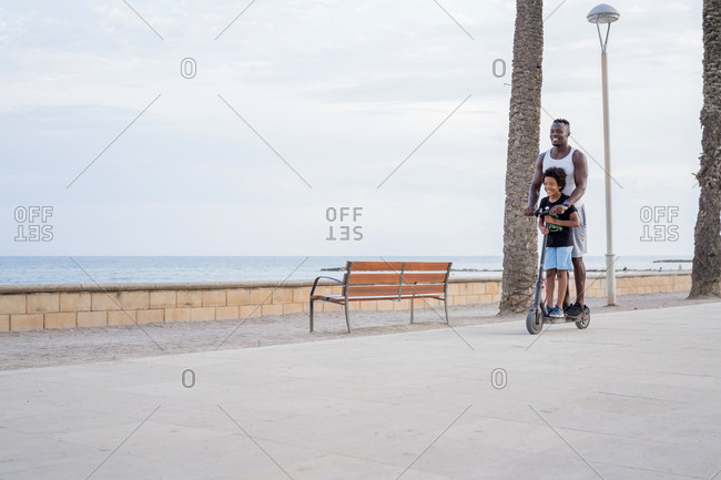 Excited African American father and son in casual clothes enjoying free time while riding electric scooter together on promenade in summer day