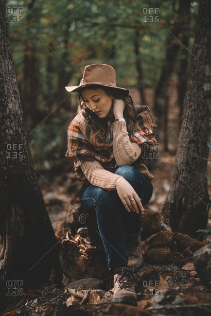 Calm young female in stylish hat and scarf sitting on ground with closed eyes and resting in green forest