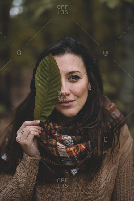 Stylish lady in knitted sweater and checkered scarf covering eye with leaf while standing on blurred background of forest