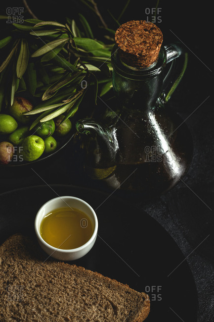 Fresh Spanish extra virgin olive oil with olives and old olive branch on dark background Healthy food Mediterranean diet.