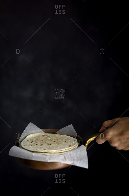 Woman's hands holding Mexican Tacos with fresh vegetables and chicken on dark background. Healthy food .Burritos