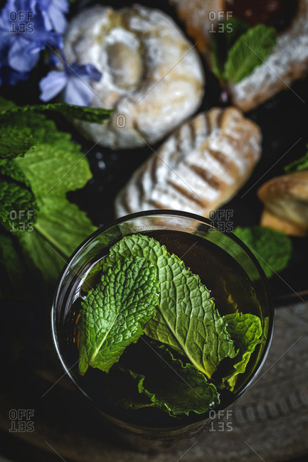 Traditional tea with mint and assorted homemade Arab sweets on dark background.