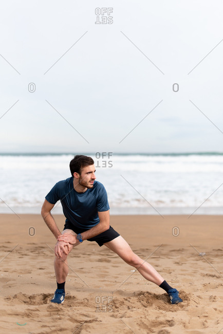 Male gymnast in sports clothing stretching legs and looking away on empty sandy beach with blue sea and sky on blurred background