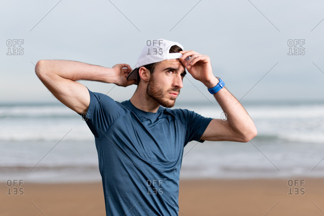 Sportsman in blue t shirt with hands behind head on white cap looking away with empty sandy seaside on blurred background