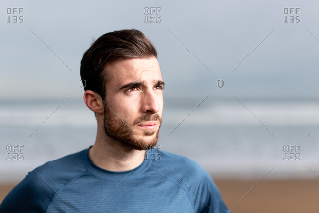 Side view of bearded sporty man in active wear taking a break after a long run on sandy empty seaside and looking away